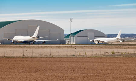 Maintenance aerodrome with planes and hangars. Airplane parking area. Industry