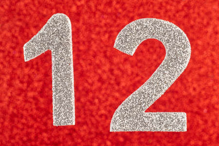 12: Number twelve silver color over a red background. Anniversary. Horizontal Stock Photo