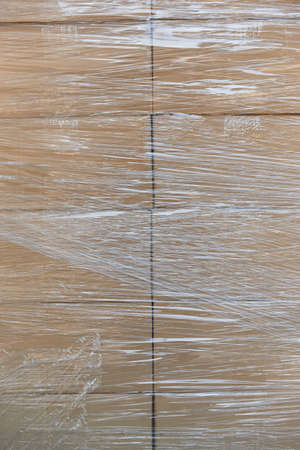 Shrink wrapping on a stacked cardboard boxes. Delivery background Stock Photo