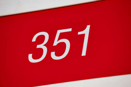 Hotel room number in red and white. Tourist apartment. Vacation Stock Photo