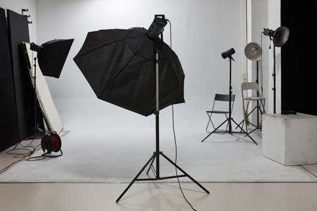 reflectors: Professional photographic studio set with flashlights and white background. Equipment