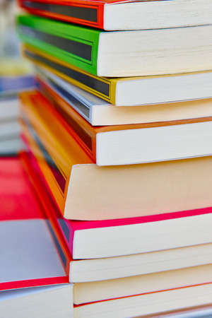 bibliography: Stacked colored books. Educational and learning background. School items. Vertical