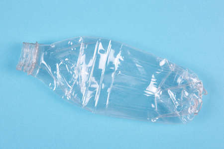 Crushed plastic bottle with blue background. Recycled garbage. Horizontal Stock Photo