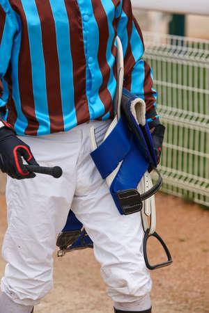 hippodrome: Jockey detail after the race. Hippodrome background. Racehorse. Competition