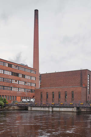 industrialised: Red brick factory building with chimney in Tampere. Finland. Vertical