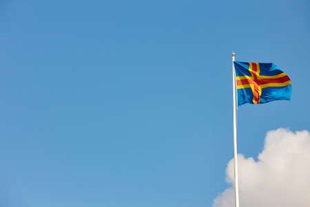 Aland islands flag over a blue sky. Finland background. Horizontal Stock Photo
