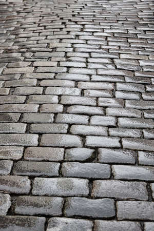 Antique wet cobblestone street at dawn. Vintage background. Vertical
