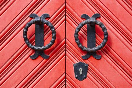 Antique metallic door knob on a red wooden doors. Horizontal
