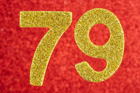 Number seventy-nine golden color over a red background. Stock Photo