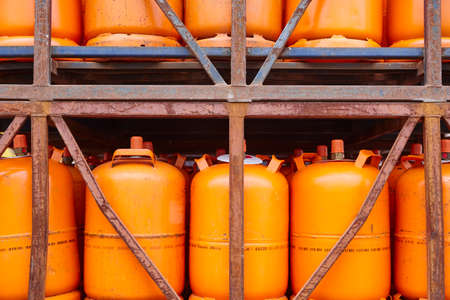 Used gas butane cylinder containers in orange tone. Horizontal Stock Photo
