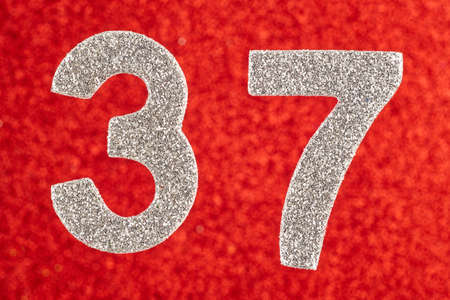 Number thirty-seven silver color over a red background. Anniversary. Horizontal Stok Fotoğraf