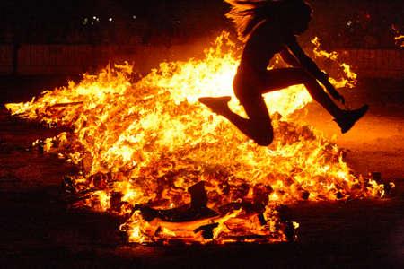 Celebración del solsticio de verano en España. Salto de mujer. Llamas de fuego. Horizontal