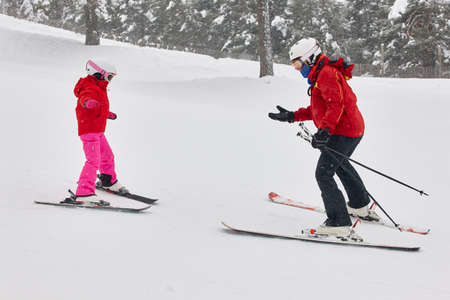 Child learning how to ski with an instructor. Winter sport 写真素材