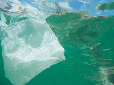 Plastic bag floating into the sea. Polluted enviromental. Recycle garbage