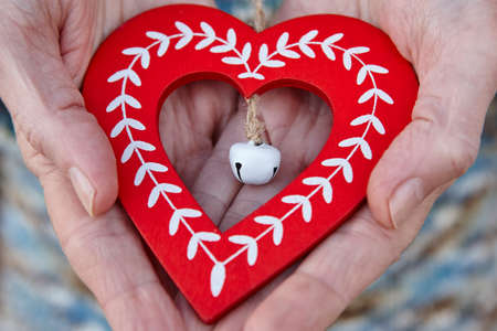 Handcrafted wooden heart. Happy christmas and tenderness between elderly people