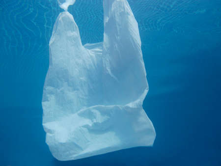 Plastic bag floating into the water. Polluted environmental. Recycle garbage Imagens