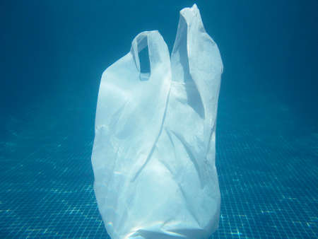 Plastic bag floating into the water. Polluted enviromental. Recycle garbage Imagens