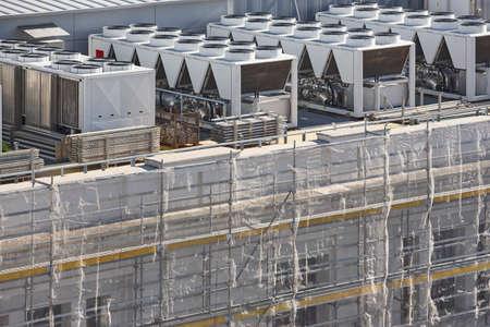 Compressori del condizionatore d'aria sul tetto di un edificio in costruzione. Industriale Archivio Fotografico