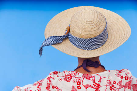 Summer time. Woman with hat and blue background. Relaxing time