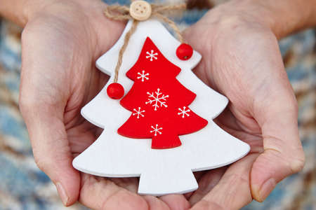 Handcrafted wooden christmas tree. Love and tenderness between elderly people.