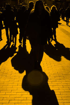 People on the street. Urban crowd in yellow tone. Vertical Stock Photo
