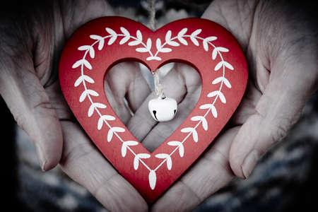 Handcrafted wooden heart. Happy christmas and tenderness between elderly people