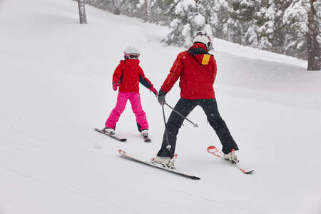 Child learning how to ski with an instructor. Winter sport Stock Photo