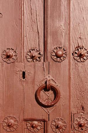 Antique classic doorknob on a brown painted wooden door. Vertical Stock Photo
