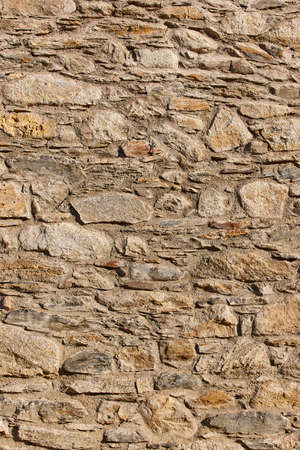 Natural stone wall facade detail. Textured rustic background. Vertical