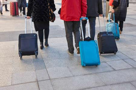 Travelers walking with luggage on the street. Urban tourism lifestyle