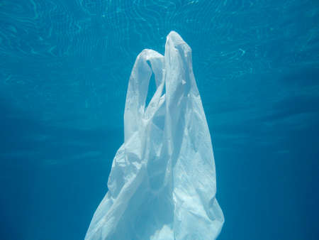 Plastic bag floating into the water. Polluted enviromental. Recycle garbage Stock Photo