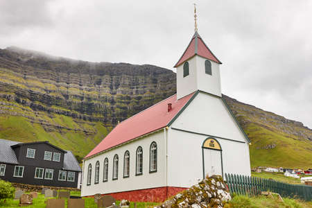 Traditional Faroe village of  Kunoy with picturesque church and mountain