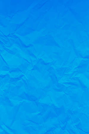 Blue crumpled wrinkled textured paper background. Empty space