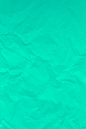 Green crumpled wrinkled textured paper background. Empty space 写真素材