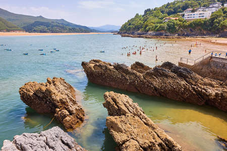Swimmers taking a bath in Euskadi coastline. Mundaka Urdaibai, Spain