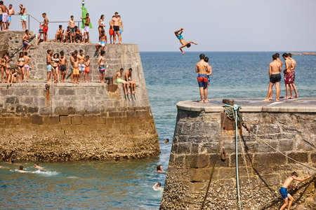 Teenagers jumping into the water. Fun time in the sea.