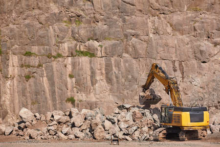 Excavator working on a stone quarry. Geological and mineral excavation