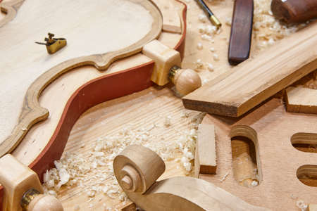 Luthier workshop with violin wooden parts and tools. Traditional craftmanship.