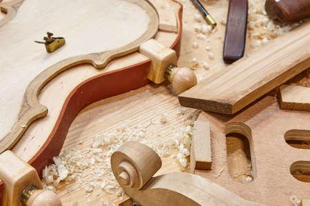 Atelier de luthier avec pièces et outils en bois de violon. Artisanat traditionnel.