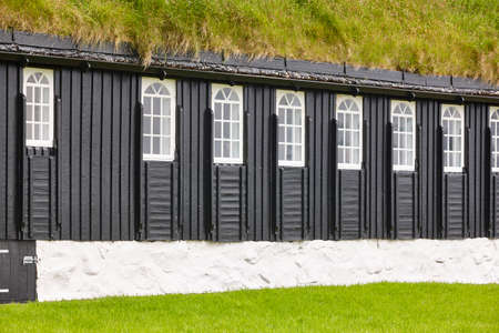 Picturesque green roof  wooden faroese black chapel facade. Faroe islands