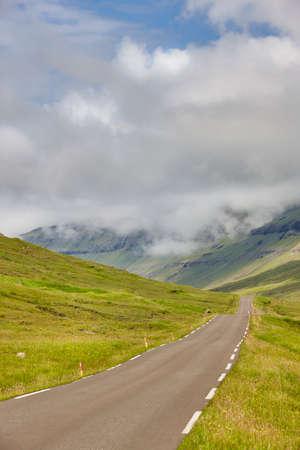 Faroe islands old road surrounded by green fjord landscape. Denmark