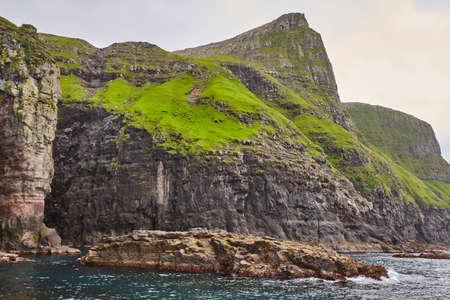 Picturesque green cliffs and atlantic ocean in Faroe islands. Reklamní fotografie