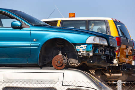 Car scrapyard. Stacked damaged vehicles ready to be recycling. Automotive Stock Photo