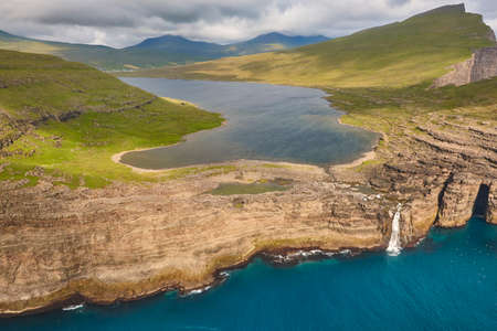 Faroe islands dramatic coastline in Vagar from helicopter. Leitisvatn lake