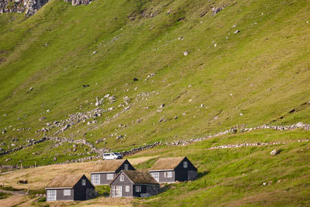 Traditional black wooden houses in Faroe Islands green landscape. Denmark