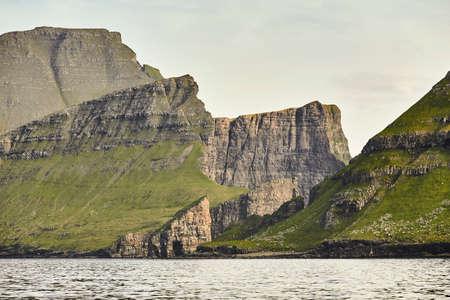Faroe islands cliffs on atlantic ocean at sunset. Stunning view.