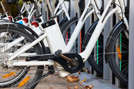 Urban electric bikes charging batteries in the city. For rent