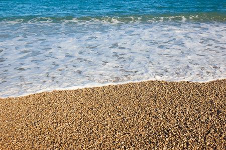 Mediterranean pebble beach and blue sea in Valencia. Spain
