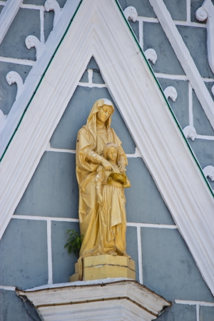 golden statue of the Virgin Mary on the wall photo