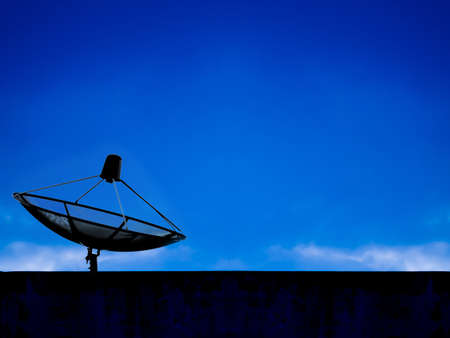 Satellite dish in blue sky photo